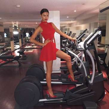 Irina Shayk stuns in the gym wearing high heels and a dress